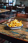 French fries in a bowl on rustic wooden table