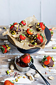 Chocolate and pistachio coated strawberries (keto cuisine)