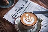 Cappuccino with latte art on a newspaper