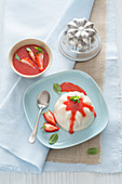 Coconut pudding with strawberry sauce and mint