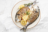 Fried sea bream with herbs and lemons