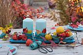 Herbst-Tischdekoration mit türkisen Kerzen, Wollschnur, Lampions und Zierquitten