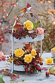 Etagere mit Rosenblüten, Hagebutten und Herbstlaub als Tischdekoration