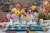 Kleine Sträuße aus Rosen und Hagebutten in Gläsern aufgereiht als Tischdekoration