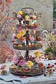 Kleine Sträuße aus Rosen und Hagebutten mit Herbstlaub auf Metall-Etagere als Tischdekoration