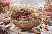 Korb mit Gräsern und Hagebutten für floristische Dekorationen