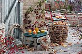Herbst-Terrasse mit Brombeere, Hagebutte, Tablett mit Kerzen, Kränze aus Clematisranken und Drahtkorb mit Herbstlaub