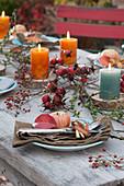 Herbstliche Tischdeko mit Hagebutten, Kerzen und Äpfeln