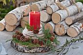 Natürliche Kerzendekoration auf Holzscheibe, dekoriert mit Wollschnur und Zweigen und Zapfen von Hemlocktanne