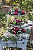 Etagere weihnachtlich dekoriert mit Kugeln, Kerzen, Tannenzweigen und Zimtstangen im Garten