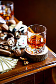 A glass of whiskey next to it, cigar, nuts and playing cards