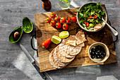 Guacamole mit Chili und Koriander serviert mit Crackern und Oliven