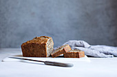 Banana bread, a piece cut against a gray background