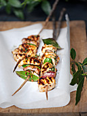 Grilled chicken skewers with bay leaves and bacon
