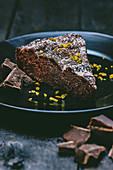 A slice of chocolate cake with icing sugar and pistachio nuts
