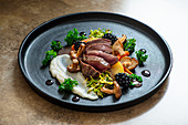 Pigeon breast with mushrooms. jerusalem artichoke puree, fondant potatoes, kale and shreded brussel sprouts with walnuts.