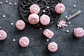 Basic macarons colored in pink and decorated with white chocolate and hearts