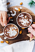 Woman and man holding a cup of vegan almond milk hot chocolate topped with coconut butter, coconut chips and almonds.