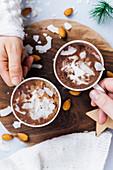 Hände halten zwei Tassen vegane heiße Schokolade mit Mandelmilch und Kokoschips