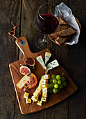 A rustic cheese platter and a glass of red wine