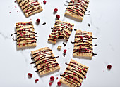 Vegan pop tarts filled with jam and topped with chocolate and dried raspberries