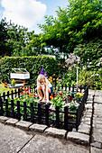 Mädchen im eingezäunten Mini-Garten