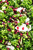 Winter salad with green kale, pomegranate seeds, peas, mozzarella and pumpkin seeds