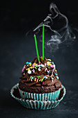 A vegan chocolate cupcake with blown-out candles
