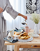 Breakfast on the table pancakesThe woman in a bathrobe pours coffee into a mug