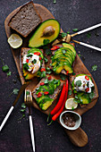 Toasts with avocado and poached egg on a wooden board