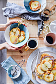 Pancakes with apples on the table with breakfast coffee mugs plates with food wooden table