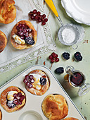 Pancake muffins, whipped cream, icing sugar, berries, maple syrup
