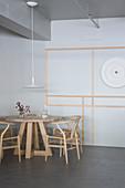 Designerstühle um runden Holztisch vor grauer Wand mit Zierleisten