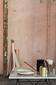 Goldene Gießkanne und Deko vor alter rosafarbener Wand