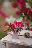 Mini-Strauß mit Geranienblüte, Fuchsie, Feder und Apfelzweig in Deko-Gießkännchen