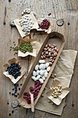 Different types of beans on a rustic wooden table