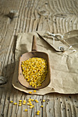 Yellow lentils on wooden scoop