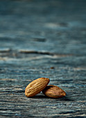 Two shelled almonds on a wooden surface
