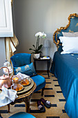 Tea and cake on a side table next to a opulent blue bed with carved golden frames