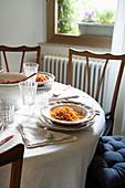Gedeckter Tisch mit Pasta auf Tellern