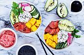 Poke Bowl mit Basmatireis, Mango, rohem Lachs, Gemüse, eingelegtem Ingwer und schwarzem Sesam