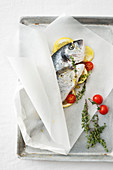 Gilt-head bream with lemon, thyme and cherry tomatoes in parchment paper