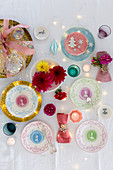 Christmas arrangement of decorative china plates, flowers and tealights