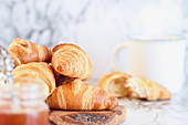 Fresh croissants with preserves and hot coffee