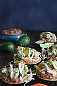 Chicken tostadas with jalapeno peppers, black olives, sour cream, lettuce, shredded chicken and fresh cilantro