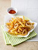 Pommes frites mit frittierten Zwiebelringen und Paprika-Chili-Pulver