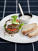 A burger sandwich with tomatoes, lettuce and a sesame seed-soya yoghurt sauce
