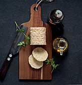 A roll of tempeh and a slices on a wooden board