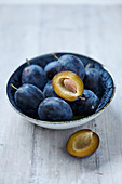 Fresh plums in a bowl on a light background