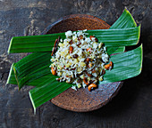 Rice with fruits and nuts served on banana leaves